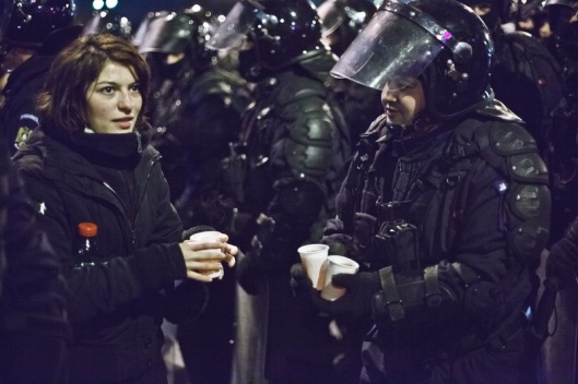 A young lady offering hot tea to the police forces in Union Square, Bucharest, Romania, Thursday 19 January 2012. Ovidiu Micsik / Inquam Photos
